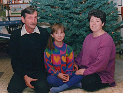 Me with my mom and dad, sitting in front of our Christmas tree when I was about eight