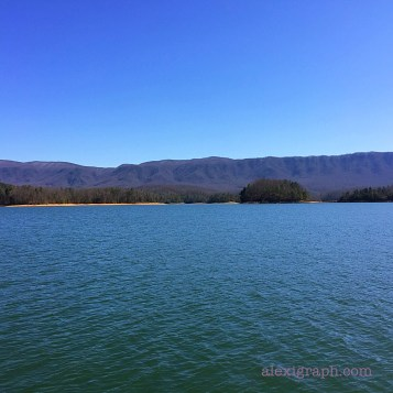 A calm lake with mountains and blue sky