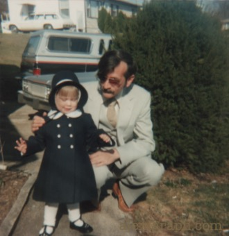 Photo of the author as a toddler, dressed for church, with her dad crouched next to her, steadying her as she walks