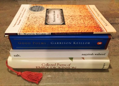 Four poetry books stacked on a counter