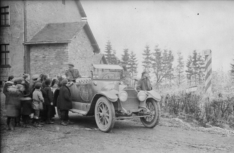 A Canadian car passing the Frontier between Belgium and Germany, surrounded by German and Belgian children. Dec. 1918. December 1918