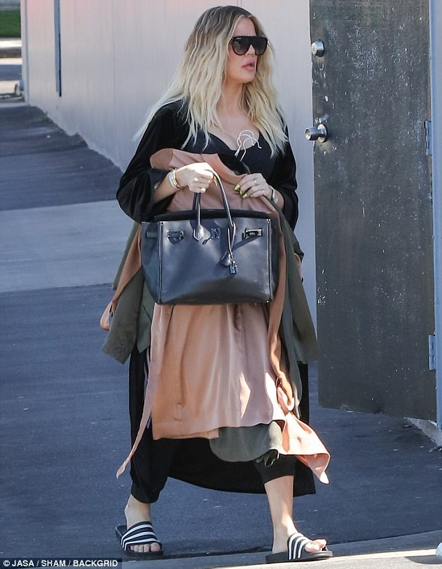 Khloe Kardashian tries to hide baby bump by carrying clothes on hangers at a studio
