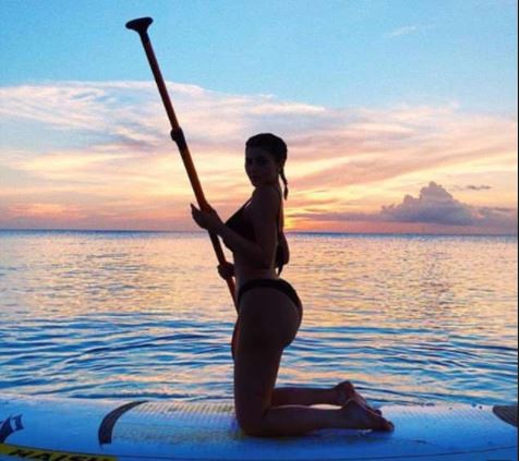 Kylie Jenner flaunts her banging bikini body as she straddles paddleboard in new sunset photos