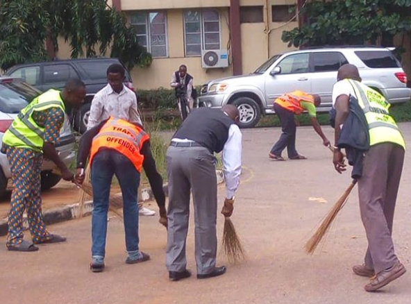 Photos: LASTMA officials force traffic offenders to sweep street and clear grass as punishment for breaking traffic rules in Lagos