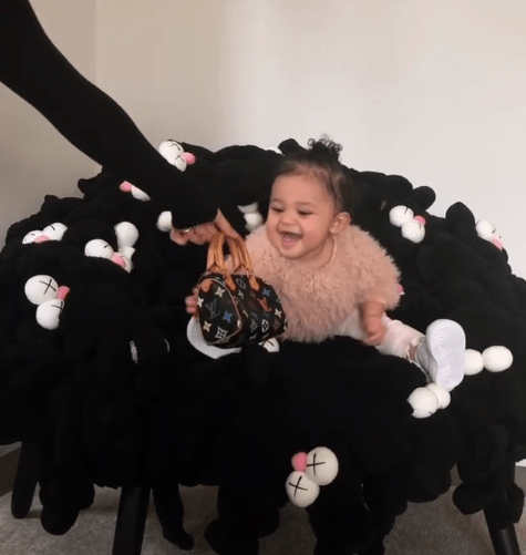 Check out 11-month-old Stormi Webster rocking the $1,100 LV bag her aunt Kim Kardashian bought for her
