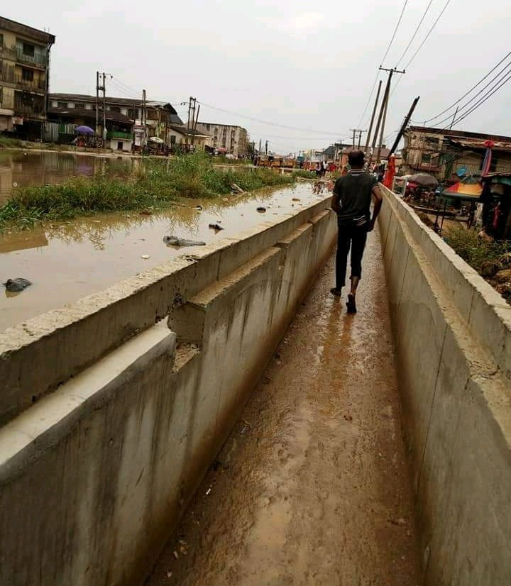 Aba resident passes through dry gutter following heavy rain that flooded roads but left the drainage dry