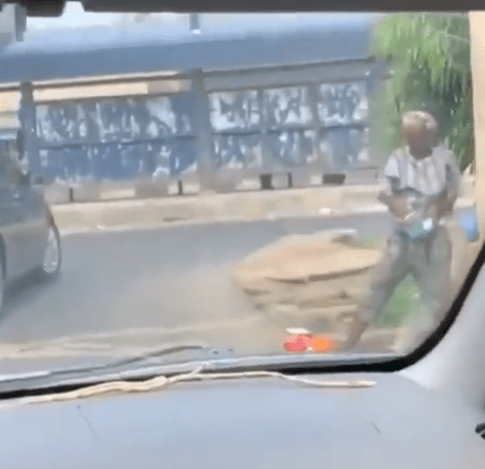 Woman seen washing plates by the roadside with