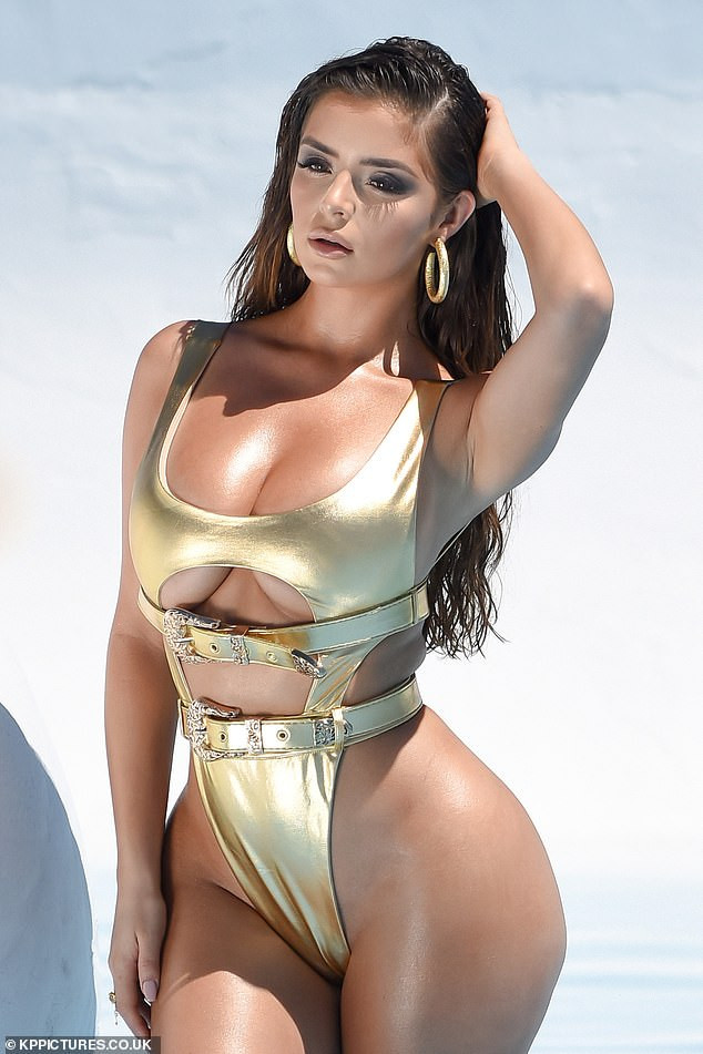 Demi Rose shows off underboob and her curvy behind in a very skimpy gold swimsuit on LA shoot (Photos)