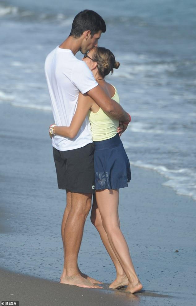 Tennis star Novak Djokovic plants a sweet kiss on wife Jelena during romantic stroll on the beach in Marbella (Photos)