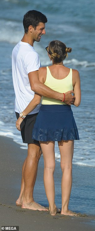 Tennis star Novak Djokovic plants a sweet kiss on wife Jelena during romantic stroll on the beach in Marbella (Photos)