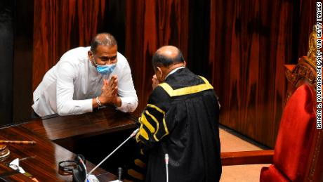 Lawmakers stage a walkout after convicted murderer on death row is sworn in by Sri Lankan Parliament