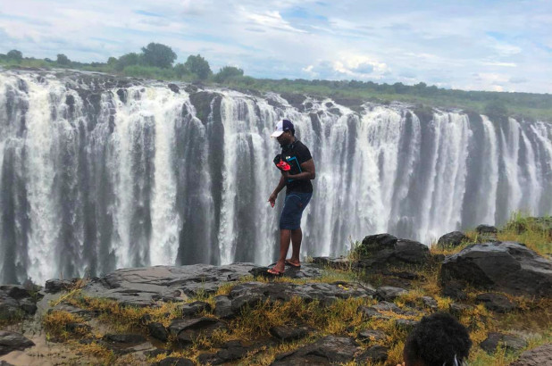 Tourist pictured near edge of Victoria Falls in Zimbabwe seconds before he fell 350 feet to his death?