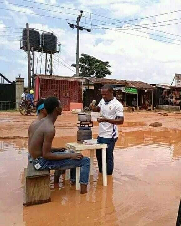 Youths cook and swim in muddy water to raise awareness about the terrible state of a road