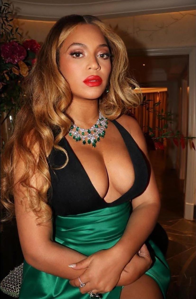 Beyonce montre son décolleté et ses cuisses alors qu'elle pose dans une robe décolletée noire et verte