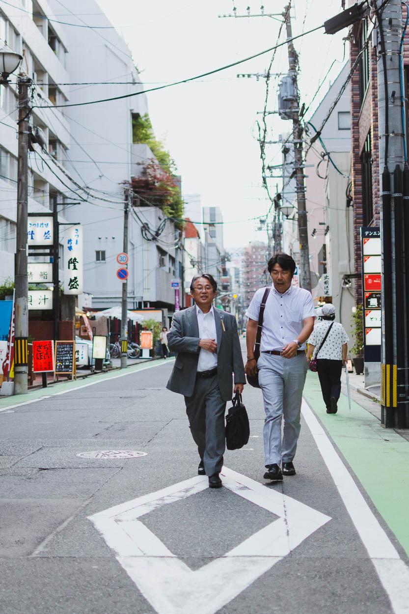 Two businessmen walk through the streets of Fukuoka