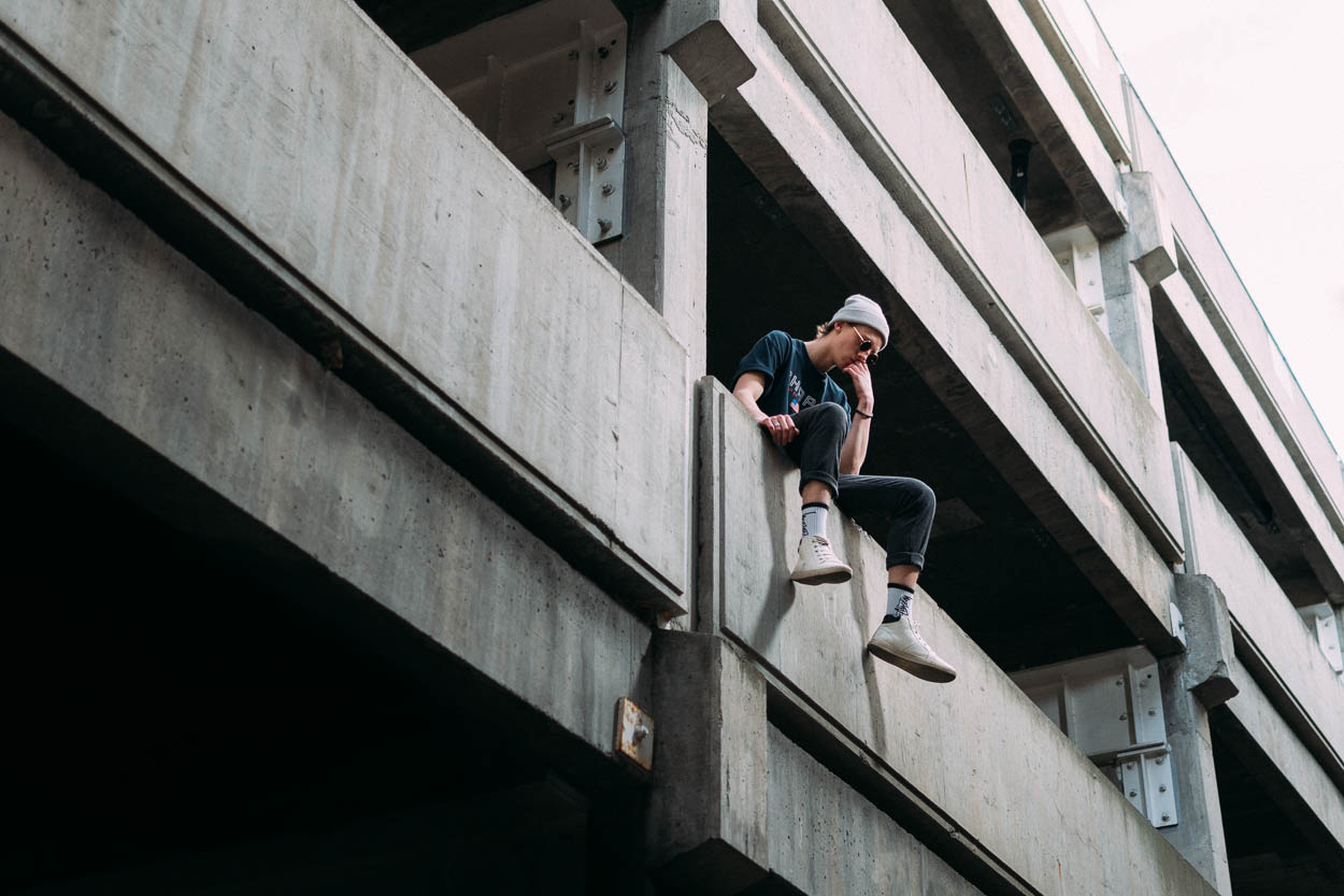 A portrait photo of a young man sitting in an urban environment.