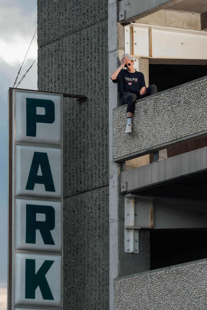 A young man sits in an urban parkade of Kamloops
