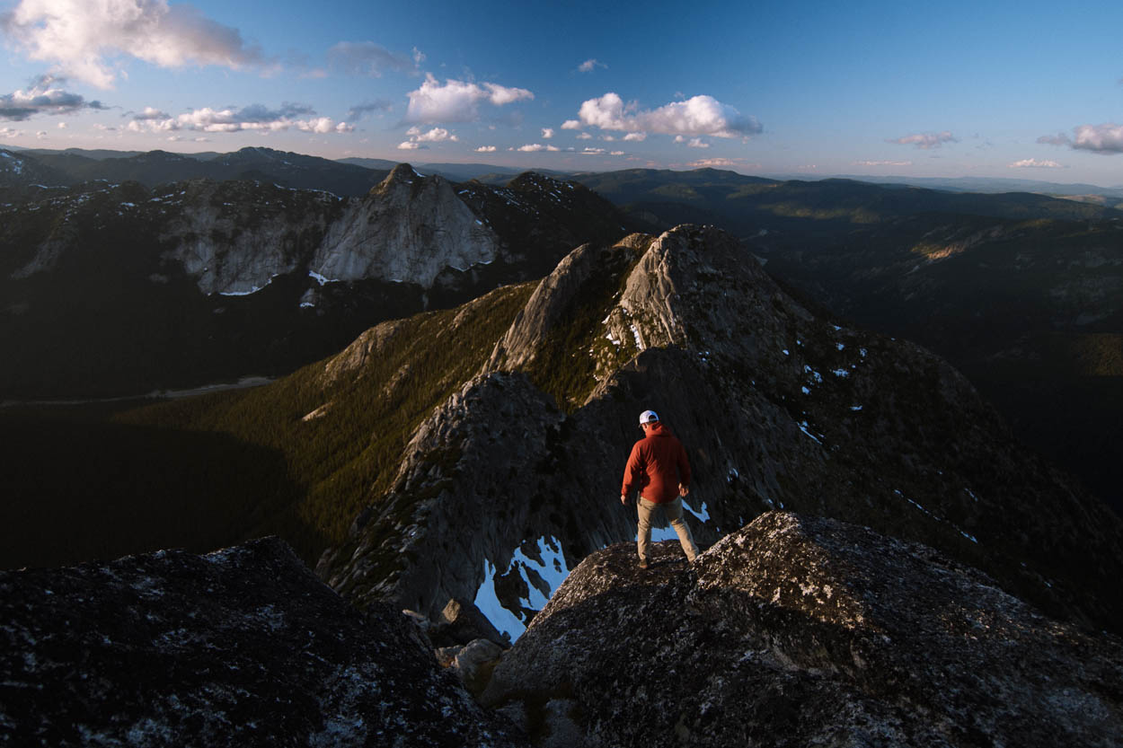 A hiker watches the sunset from Needle Peak, Coquihalla Recreation Area