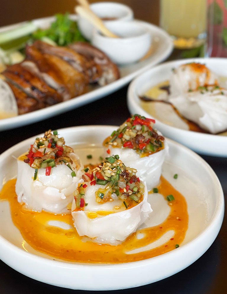 A plate of scallop dumpling topped with cucumber chilli XO and red yuzu