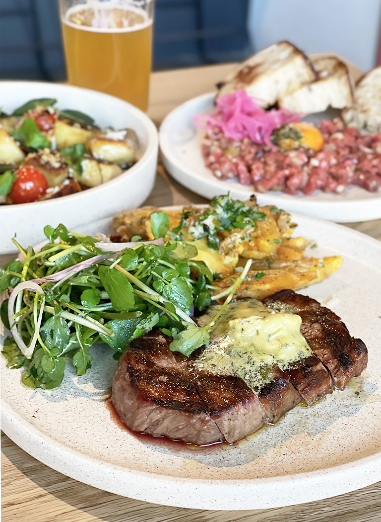 A plate of wood-grilled Black Angus sirloin with anchovy butter, watercress salad and crispy Kipfler potatoes from Besk