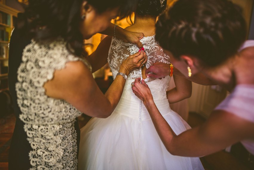 bride putting on beautiful wedding gown