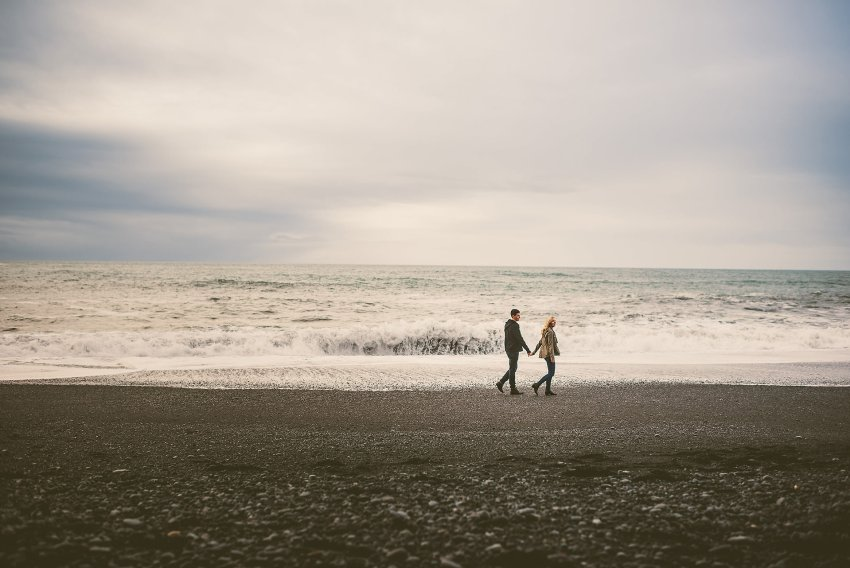 couple walking on black sand beach in Iceland