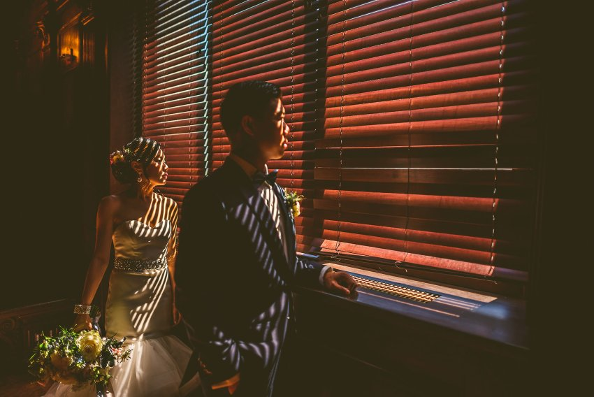 Dramatic wedding photo by shuttered blinds