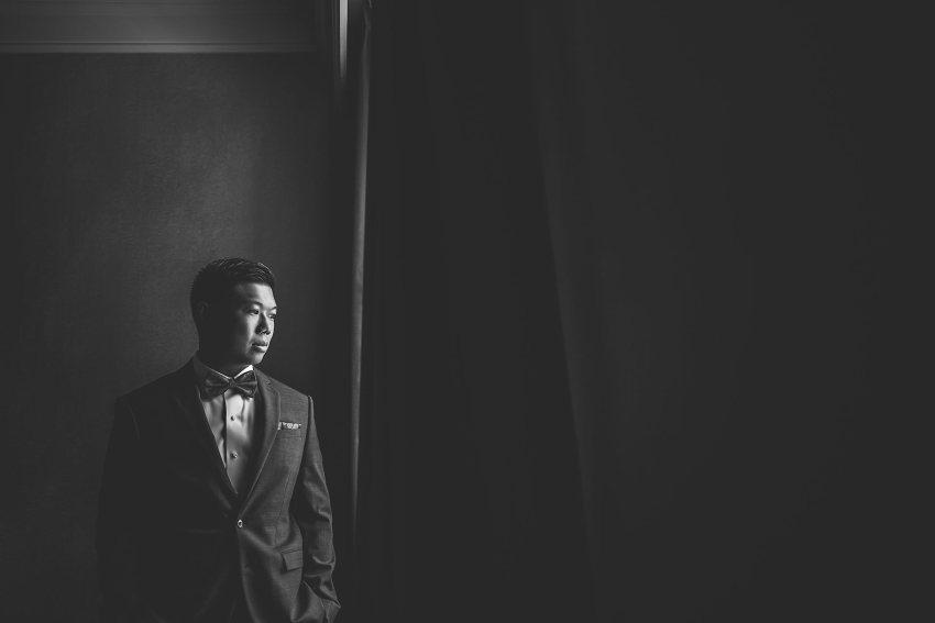 Stoic groom portrait by window