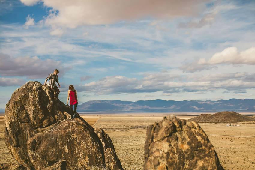 Couple walking down rocks in Kingman