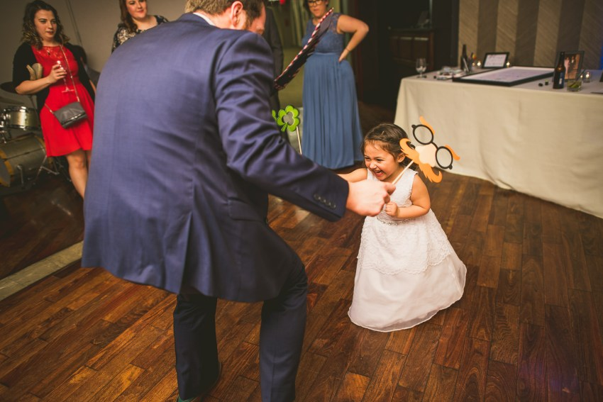 flower girl playing with groomsman