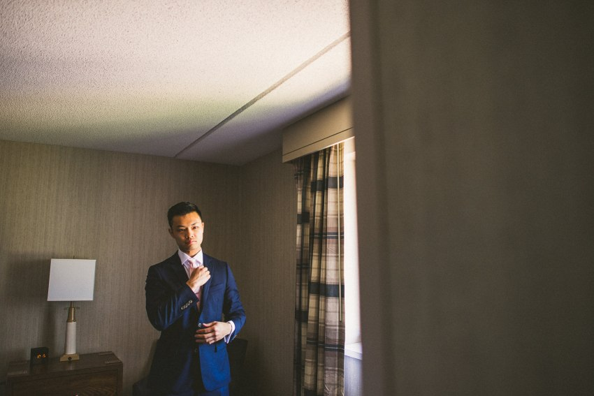 Groom tying wedding tie