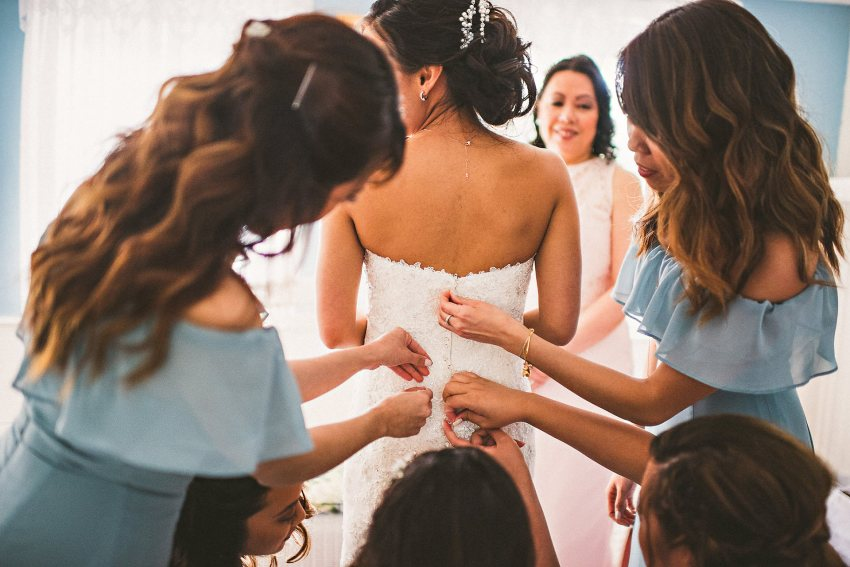 Bridesmaids helping with wedding gown
