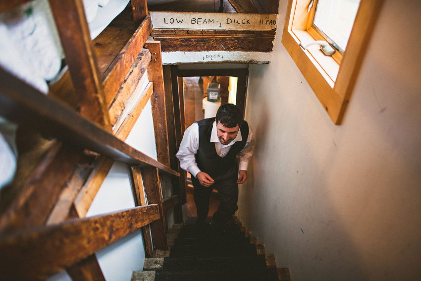 Groom walking up stairs to attic