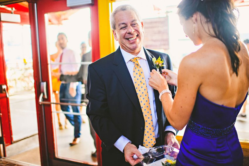 Bride putting boutonniere on father in law