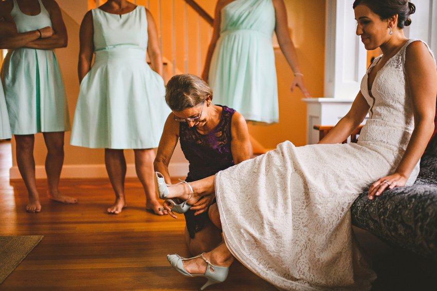 Bride's mother putting on shoes
