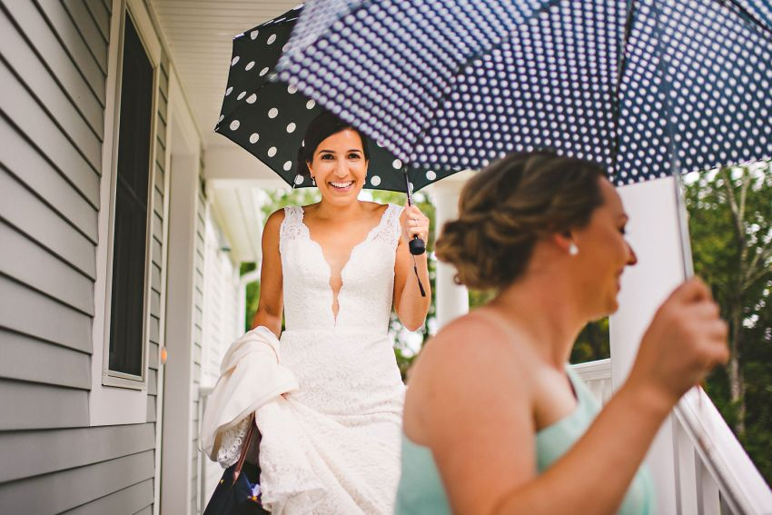 Bride leaving house with umbrella