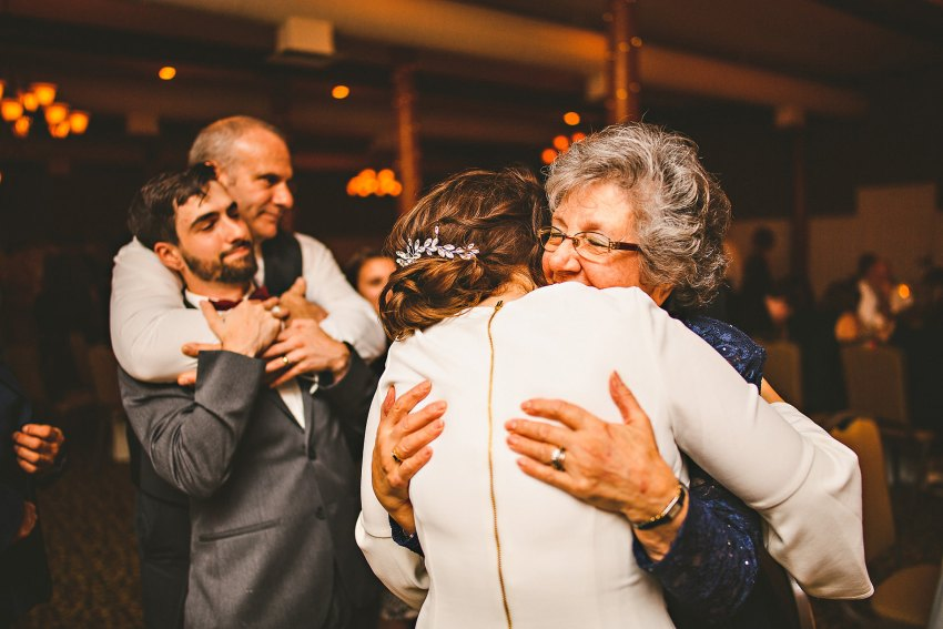 Bride and groom hugging family