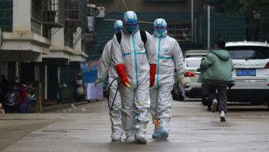 عاملون يرتدون ملابس واقية حماية من فيرو الكورونا محاولة لتجنب الاصابة به