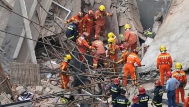 عمال يعملون على ازالة انقاض الانهيار للمبني في الصين