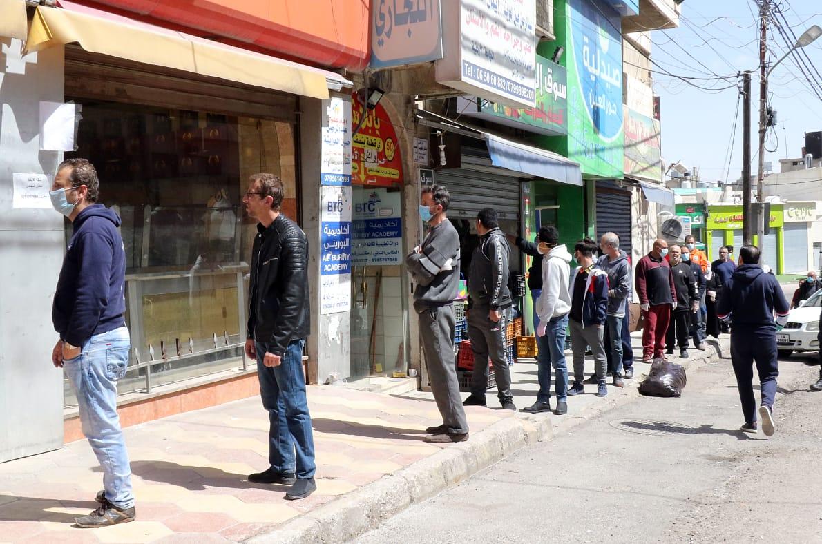 مواطنون يصطفون أمام أحد المحال التجارية لشراء حاجياتهم في عمان أمس - تصوير أمجد الطويل