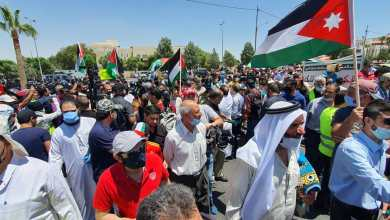 مشاركون في الوقفة يرفعون الأعلام الأردنية - تصوير: محمد مغايضة