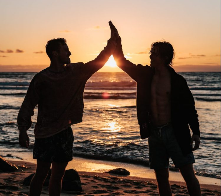 2 friends on the beach at sunset exchanging high-fives