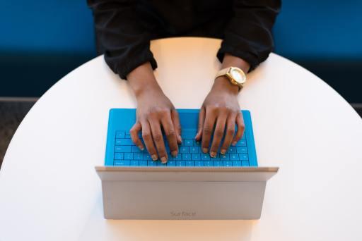 hands working on blue keyboard