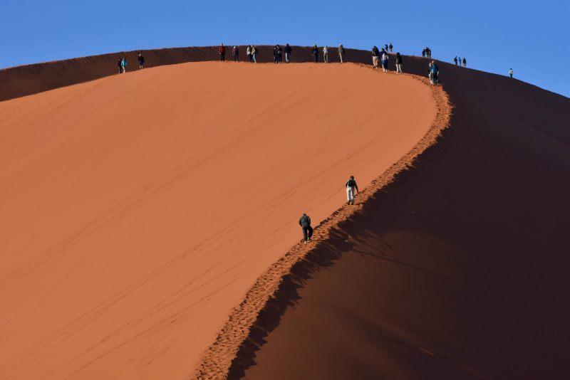 אנשים עולים לדיונה בנמביה