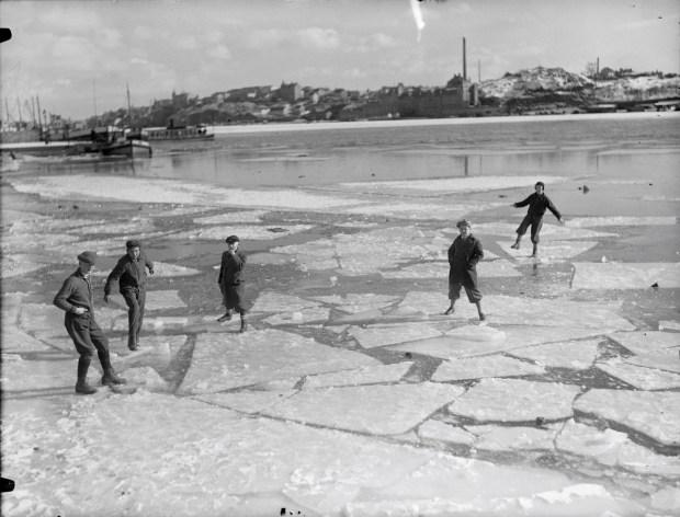 FOTOGRAFI Pojkar jumpar på isflak vid Norr Mälarstrand. I fonden Södermalm. 1930-1930 FOTOGRAF: Okänd. Aftonbladet BILDNUMMER: AB 68 Stadsmuseet i Stockholm