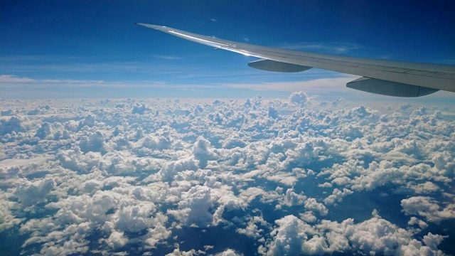 How to apply for a New Zealand Working Holiday Visa, Flying into New Zealand with view of plane wing and fluffy clouds