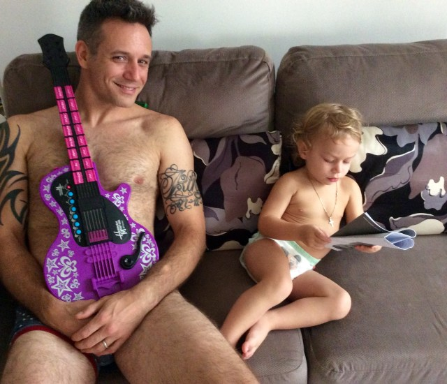 Dad and son enjoying a lazy weekend on the couch reading newspapers and making tunes