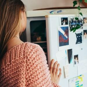 Woman storing food n refrigerator