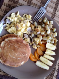Scrambled eggs, pancakes, and pink lady apples