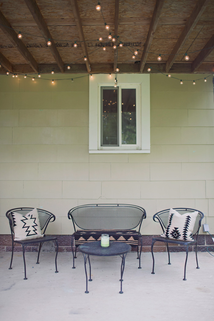Back porch decorated with wrought iron patio set and patio string lights